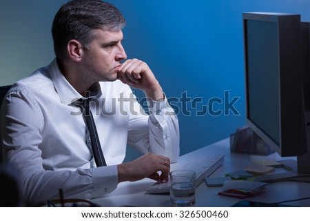 Middle aged thoughtful man working on computer - stock photo