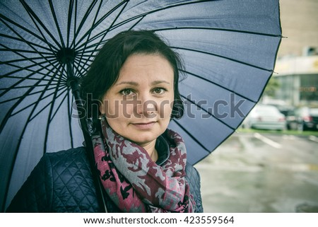 """Middle-aged, tired woman under an umbrella. Street Photography. """"Real People"""" series.  - stock photo"""