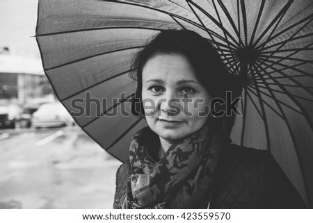 """Middle-aged, tired woman under an umbrella. Street Photography. """"Real People"""" series. Monochrome black and white photo - stock photo"""