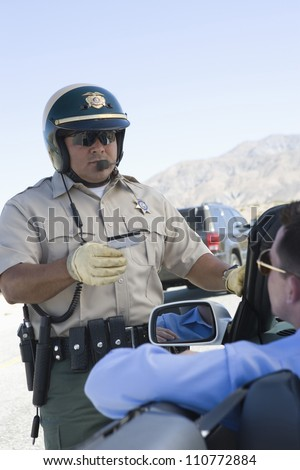Middle aged traffic cop checking driving license - stock photo