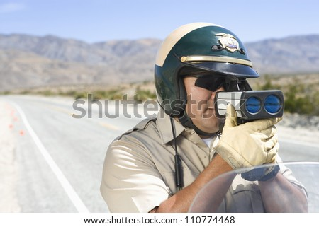 Middle aged traffic officer looking through radar gun - stock photo