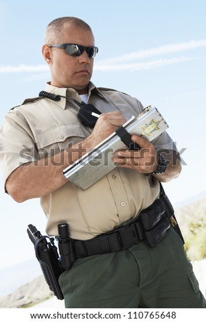 Middle aged traffic policeman writing on clipboard - stock photo