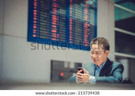 Middle-aged Vietnamese businessman using smartphone while waiting at the airport - stock photo