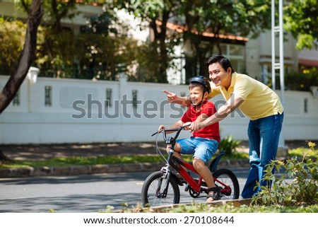 Middle-aged Vietnamese man teaching his son to cycle - stock photo