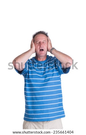 Middle aged white man in a blue striped shirt holding his hands over his ears while he is screaming in frustration or anger and pain