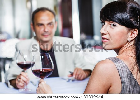 Middle aged woman and her husband having romantic dinner in a cozy restaurant - stock photo