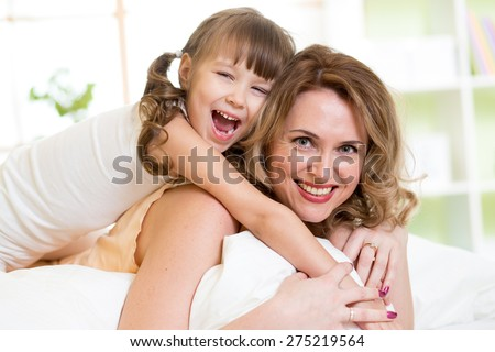 Middle-aged woman and kid girl in bed playing and smiling - stock photo