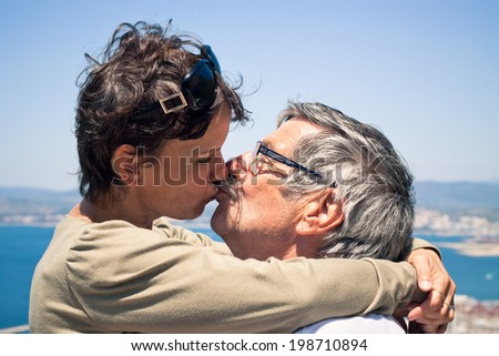 Middle aged woman and senior man in love kissing outdoors.