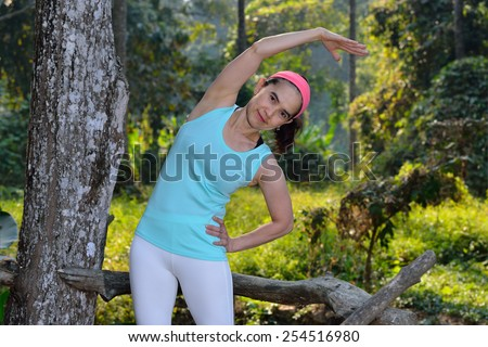 Middle aged woman bending over to do stretching in the park - stock photo