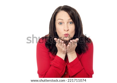 Middle aged woman blowing a kiss in air - stock photo