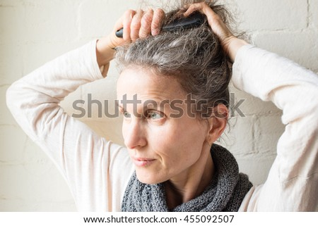 Middle aged woman brushing grey hair