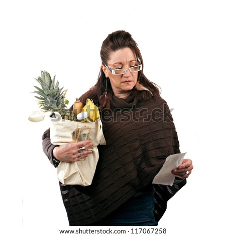 Middle aged woman carefully reviewing her sale receipt and reviewing her grocery shopping bill.