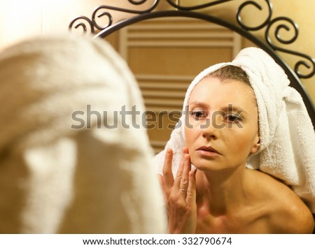 Middle-aged woman checking her face in bathroom mirror after shower - stock photo