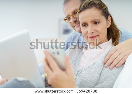 Middle-aged woman checking her mobile phone reading a text message as she relaxes at home on the sofa with her husband