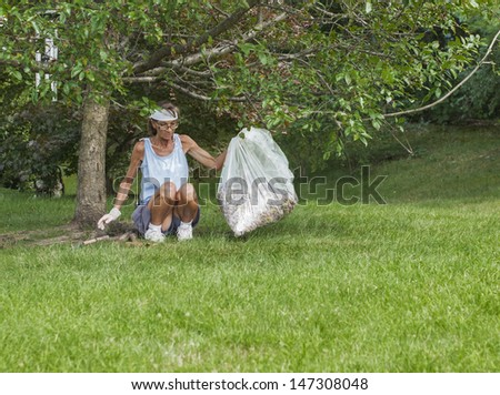 Middle aged woman cleans tree leaf litter from summer lawn.