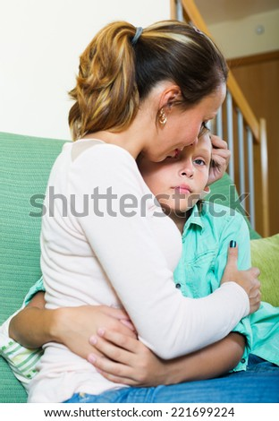 middle-aged woman comforting crying teenager son