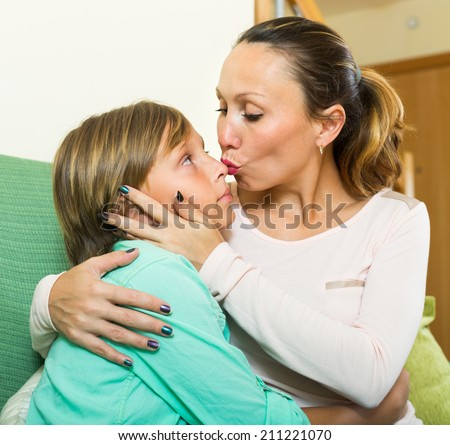 middle-aged woman consoling crying teenage son at home
