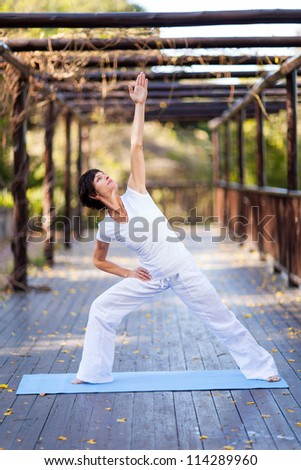 middle aged woman doing exercise workout outdoors - stock photo