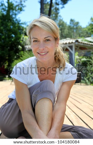 Middle-aged woman doing fitness exercises outside - stock photo