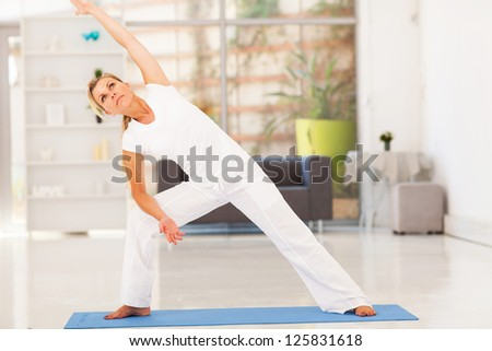 middle aged woman doing fitness workout at home - stock photo