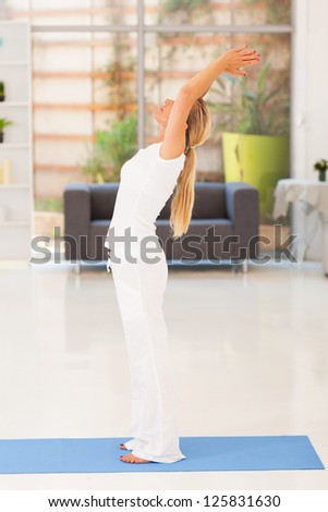middle aged woman doing yoga at home - stock photo