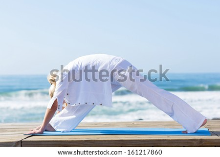 middle aged woman doing yoga exercise by the beach