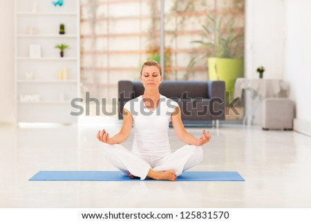 middle aged woman doing yoga meditation at home - stock photo