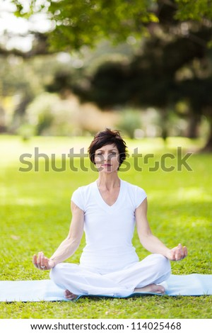 middle aged woman doing yoga meditation outdoors - stock photo