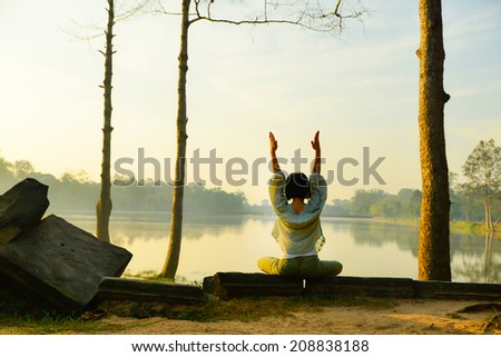 middle aged woman doing yoga outdoors in forest  - stock photo