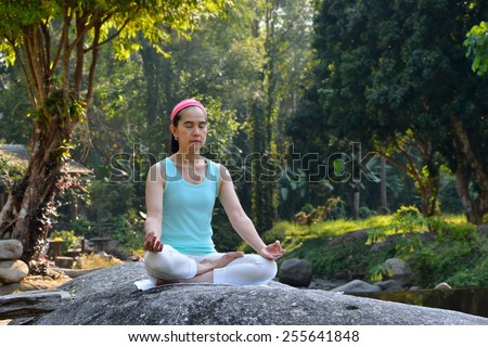 Middle aged woman doing yoga posture outdoor - stock photo