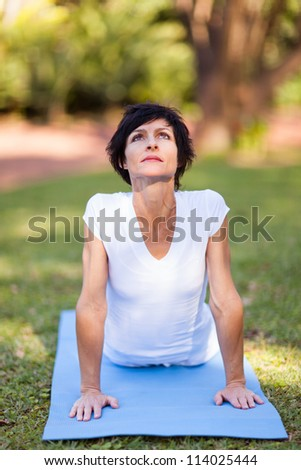 middle aged woman doing yoga stretching outdoors - stock photo