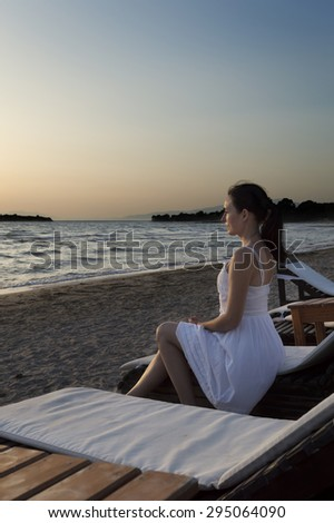 middle aged woman dressed in white sits on sun lounger on the beach and looks at sunset. Sun lounger stands on sand with Sea and sky visible in background
