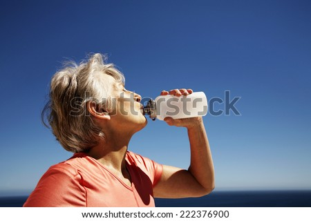 Middle-Aged Woman Drinking Water After Workout - stock photo