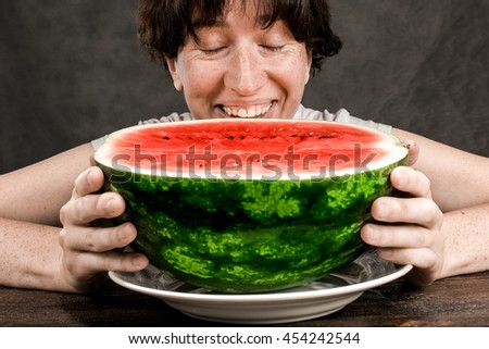 Middle-aged woman eating a half of red melon over dark  background. - stock photo