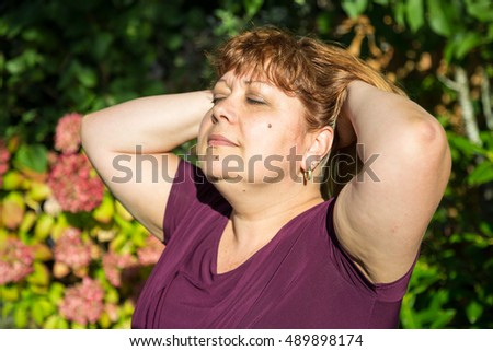 Middle aged woman enjoying the sun during a sunny summer day in nature.