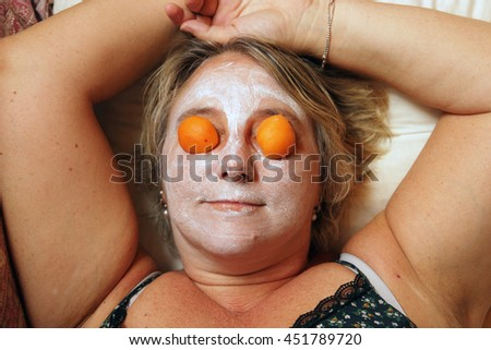 middle-aged woman having beauty mask at home