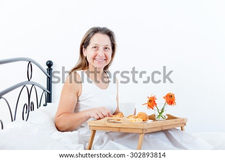 Middle-aged woman having breakfast in bed coffee with croissants.