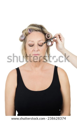 Middle aged woman having her makeup done against a white background - stock photo