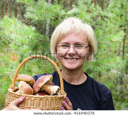 middle-aged woman holding a basket with edible mushrooms