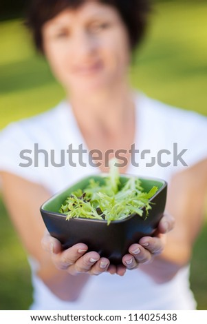 middle aged woman holding a bowl of green salad with both hands - stock photo