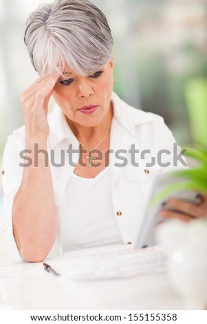 middle aged woman holding a calculator and making payment - stock photo