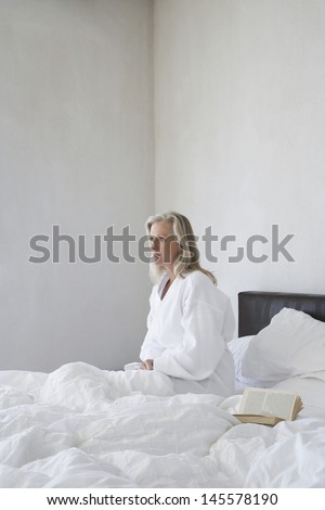 Middle aged woman in bathrobe sitting next to open book on bed