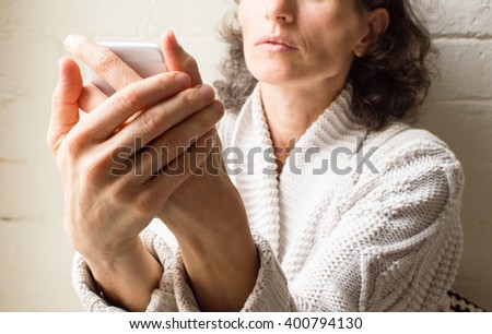 Middle aged woman in grey cardigan holding smart phone (selective focus)