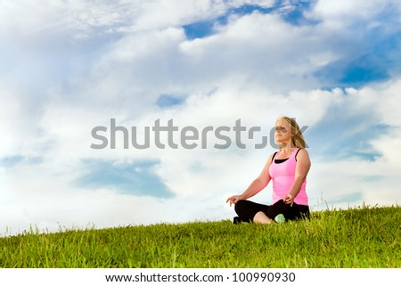 Middle-aged woman in her 40s meditating for exercise outdoors - stock photo