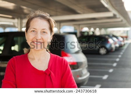 Middle-aged woman in  red dress at car parking lot. - stock photo