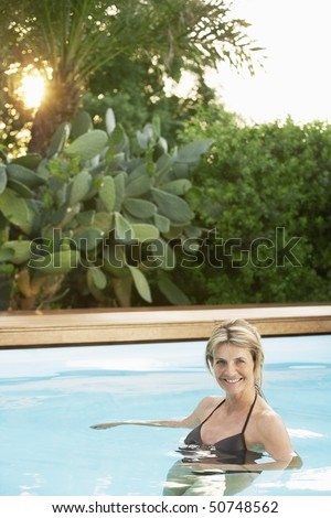 Middle-aged woman in swimming pool, portrait - stock photo