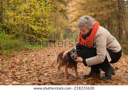Middle aged woman in the autumn forest with her dog