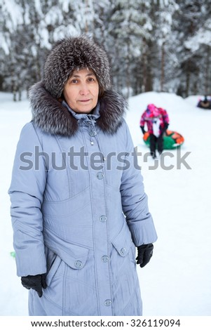 Middle-aged woman in winter clothing close-up on a background of the child sledding - stock photo