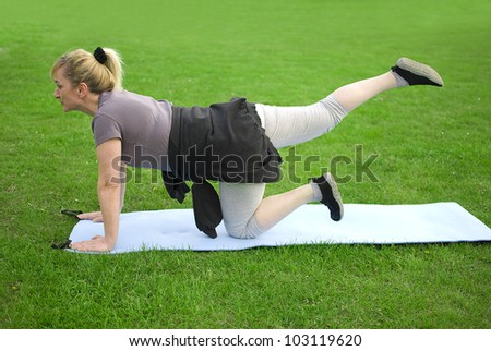 middle aged woman keeping fit with exercises in a park - stock photo