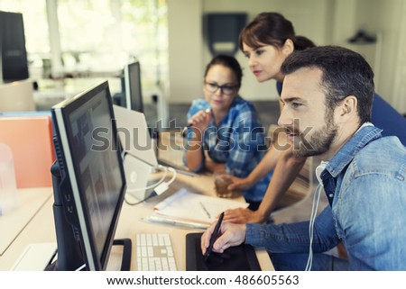 Middle aged woman manager working on computer with her team in modern startup office